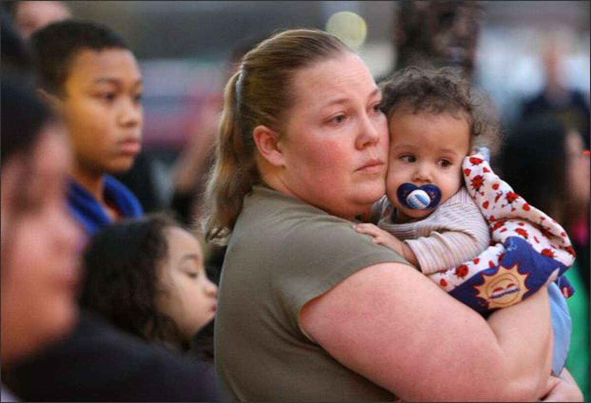 Molly Reyes of Renton holds her son Kendrick, 7 months, while watching police clear Southcenter Mall after a shooting. Reyes said she was shopping when she heard two shots, then ran with a crowd into a store and hid for about 20 minutes until police came and escorted them out of the mall.