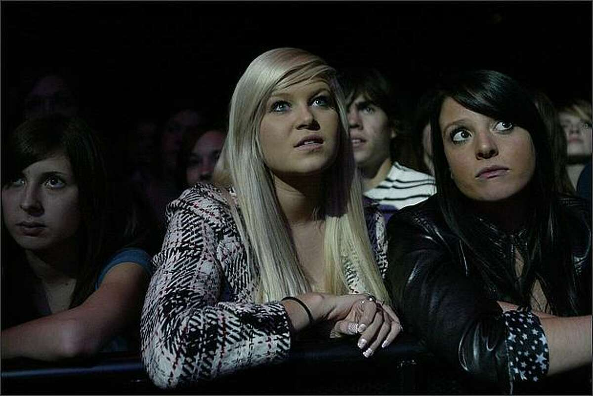 Kayla Burnham, left, and Kasandra Evans (both of Olympia) listen to Aqueduct perform at the 2008 Deck The Hall Ball concert at the WaMu Theater.