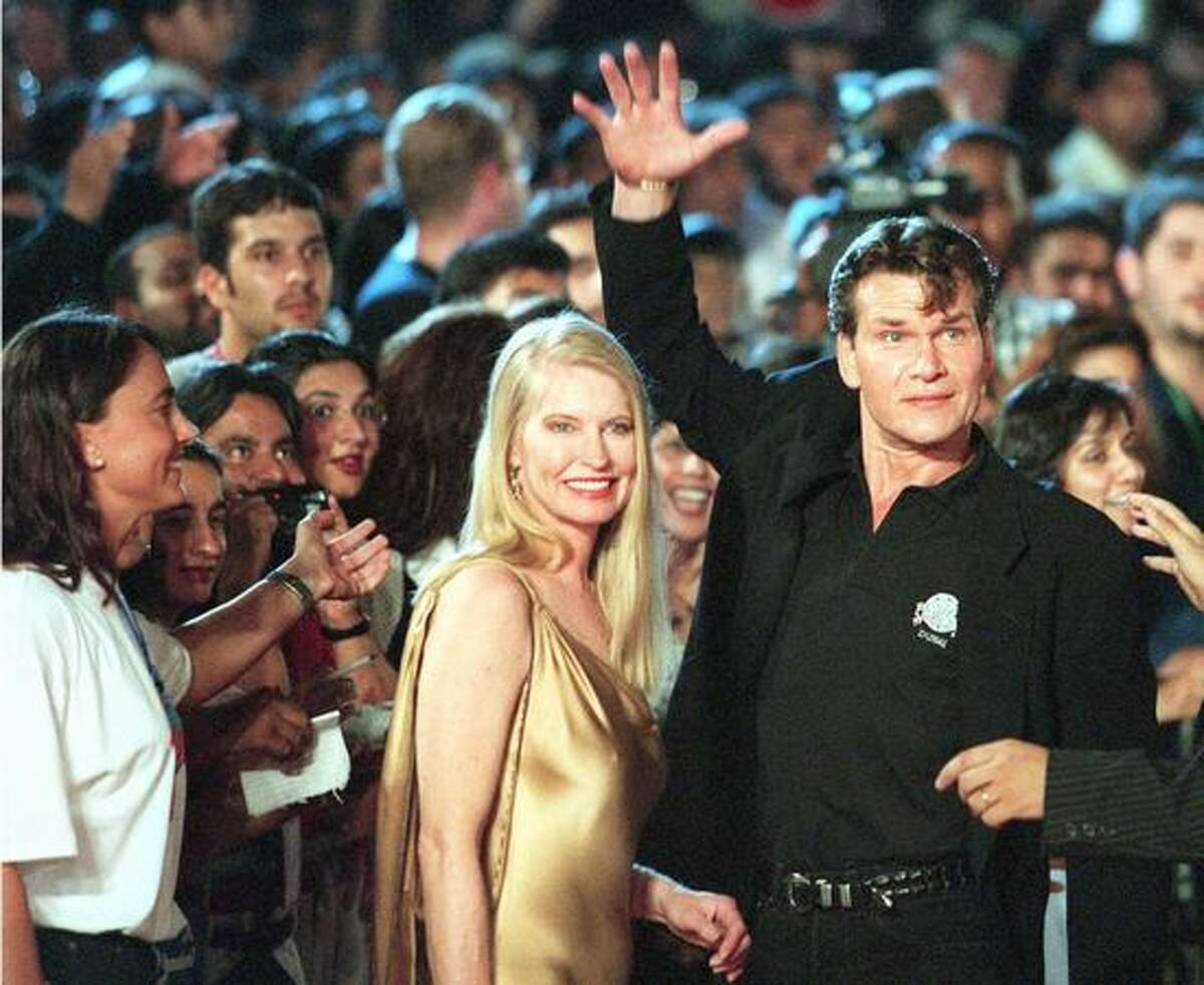 Actor Patrick Swayze waves to the crowd gathered for the opening of the new Planet Hollywood restaurant in Dubai on May 26, 1998.