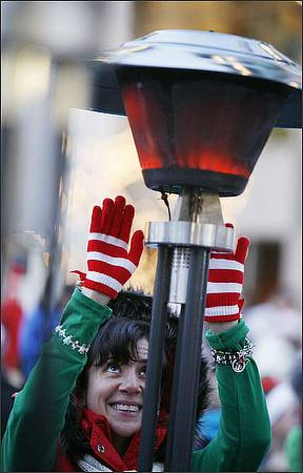 Jennifer Covey tries to stay warm before the start of the 24th Annual Jingle Bell Run. Photo: Paul Joseph Brown, Seattle Post-Intelligencer