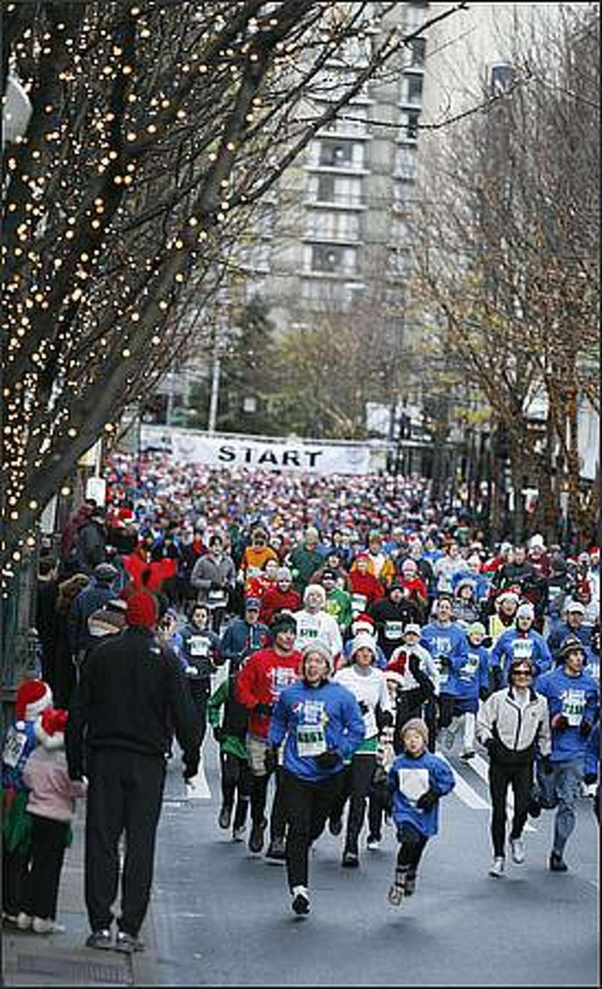 Participants in the 24th Annual Jingle Bell Run 5K run up Fifth Avenue.