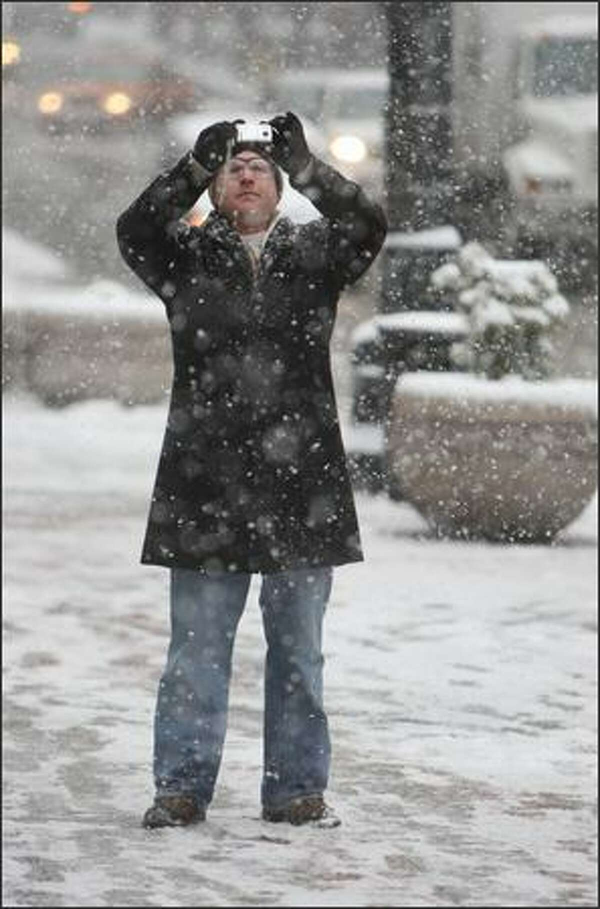 Belltown resident Aaron Gaurley snaps a picture of falling snow in Seattle on Thursday.