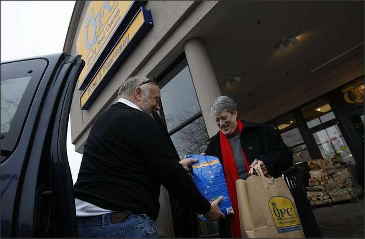 David and Lynn Auld pack up their car with groceries from QFC before heading back to their home in Queen Anne before Saturday's snowstorm.