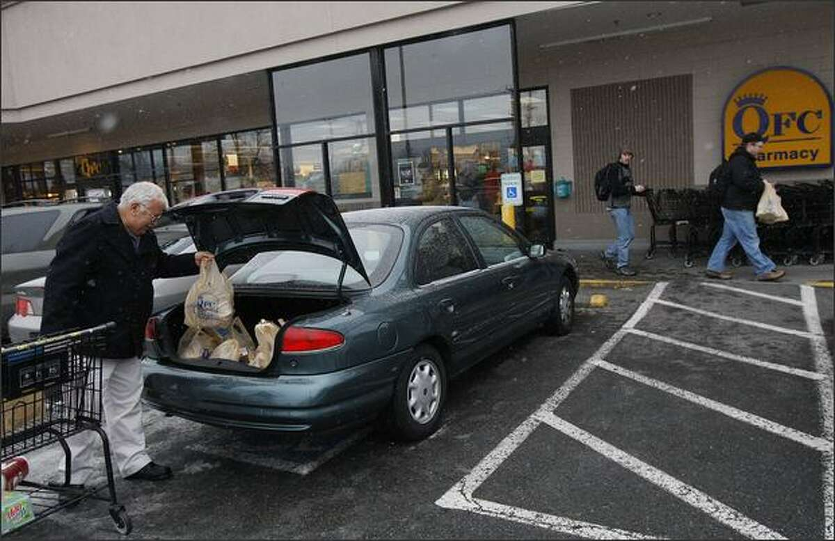 Richard Hiddleston packs up his car with groceries from QFC.