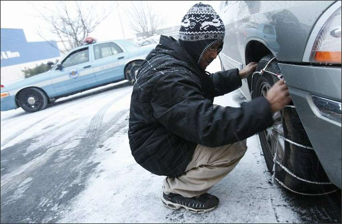 Dave Bajra chains up his minivan outside of Schucks Auto Supply.