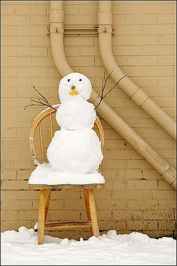 A small snowman takes a load off in the Wallingford neighborhood of Seattle. Dec. 22, 2008. Photo: Andy Rogers, Seattle Post-Intelligencer