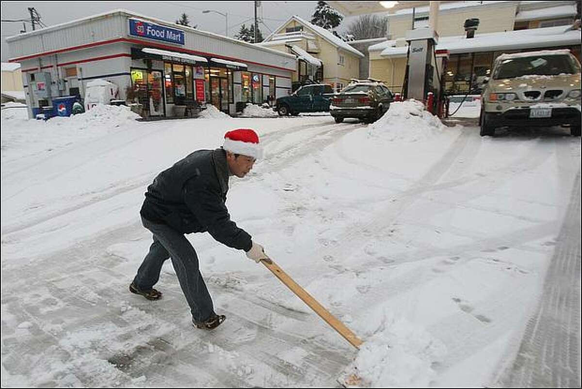 James Kim of Federal Way shovels snow with a homemade shovel in front of his gas station in the Seattle neighborhood of Magnolia Wednesday morning. Kim made the shovel out of a board and a piece of plywood after he found that all area stores had sold out of shovels.