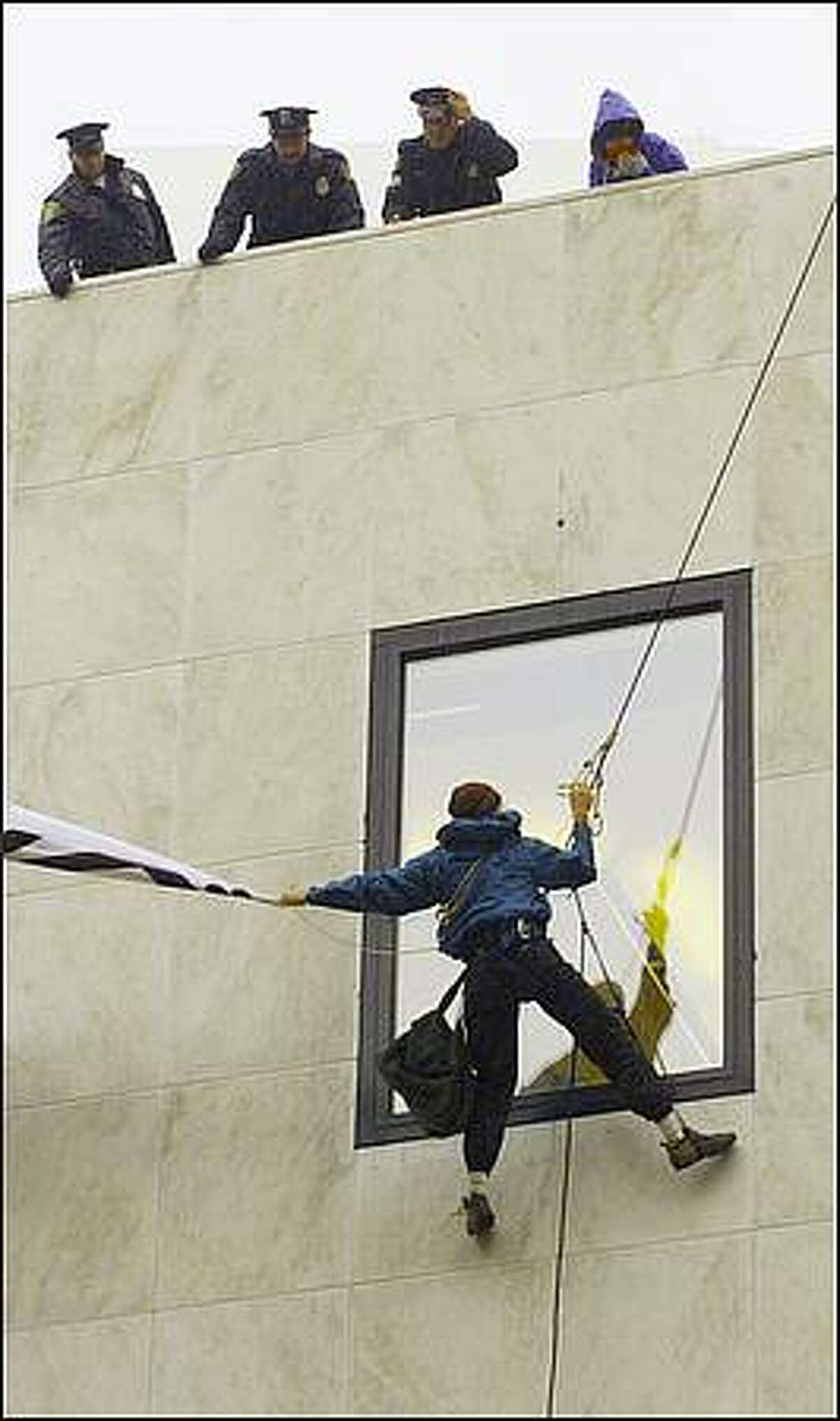 Photo By Mike Urban Seattle Post-Intelligencer 11/22/99 - WTO protestor Seth Quackenbush releases a cloth protest sign before ascending his climbing ropes into the hands of waiting Seattle police officers atop the Old Navy store in downtown Seattle. Quackenbusk and a fellow protestor hung from the building for about two hours before being arrested.