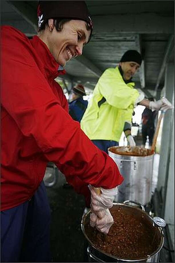 Timea Tihanyi and her husband Sandor Kovacs stir large pots of warm chili on hand for chilly runners participating in the Resolution Run 5K and Polar Bear Dive at Magnuson Park on New Year's Day. Photo: Paul Joseph Brown, Seattle Post-Intelligencer