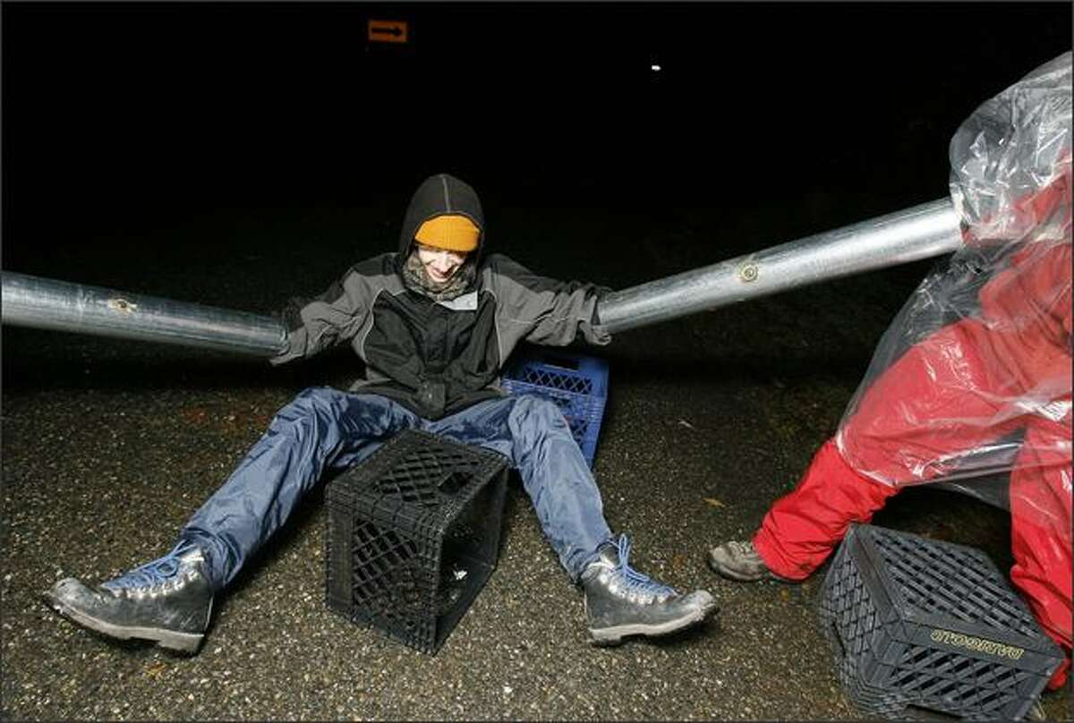 """Hindered by the pitch darkness and the steel tubes attached to his arms """"hard blockade team"""" member Benjamin Fulton falls off his milk-crate seat during a protest against Glacier's mining operation on Vashon Island."""