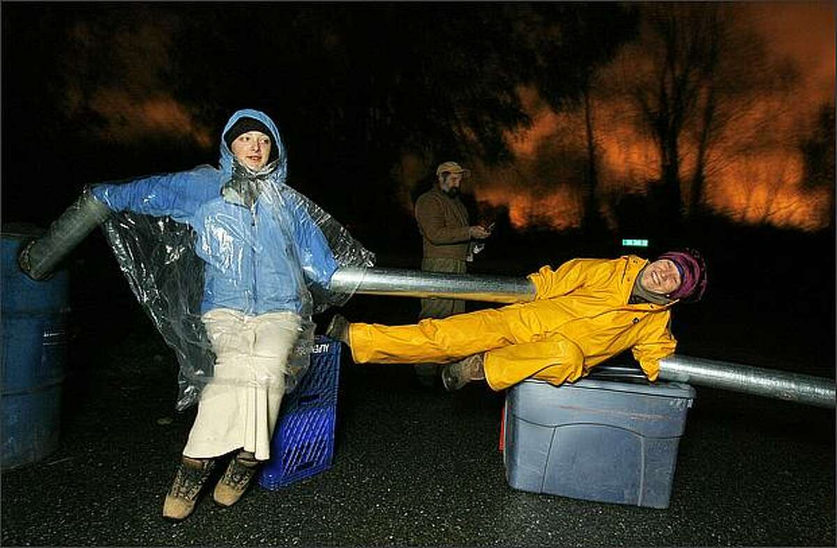 """""""Hard blockade team"""" member Nan Draper (right) tries to keep her body limber with yoga moves as she and fellow protester Morgan Guion (left) block a public access road during a protest against Glacier's mining operation on Vashon Island."""
