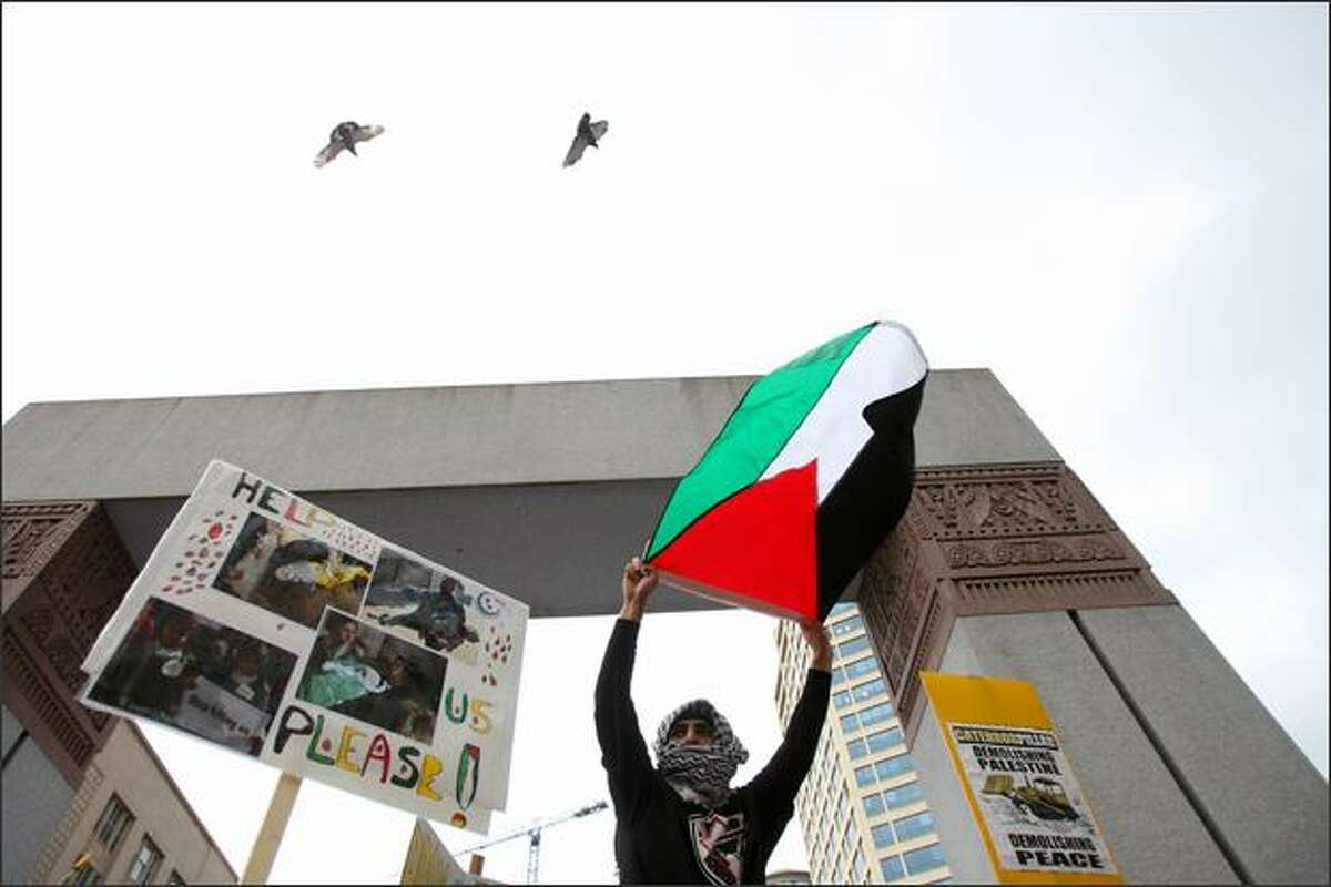 A supporter of Palestine waves a Palestinian flag at Westlake Plaza on Saturday after a march through downtown Seattle in protest of Israeli attacks against Hamas in Gaza.