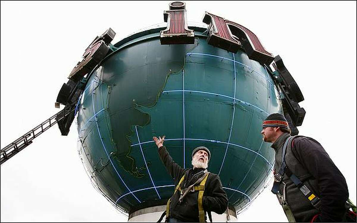 Dave DeFrank, who has been maintaining the Seattle Post-Intelligencer's signature neon globe since 1968, talks about the state of the neon - damaged in a recent snowstorm - with Andy Colton, who DeFrank has trained to maintain the globe.