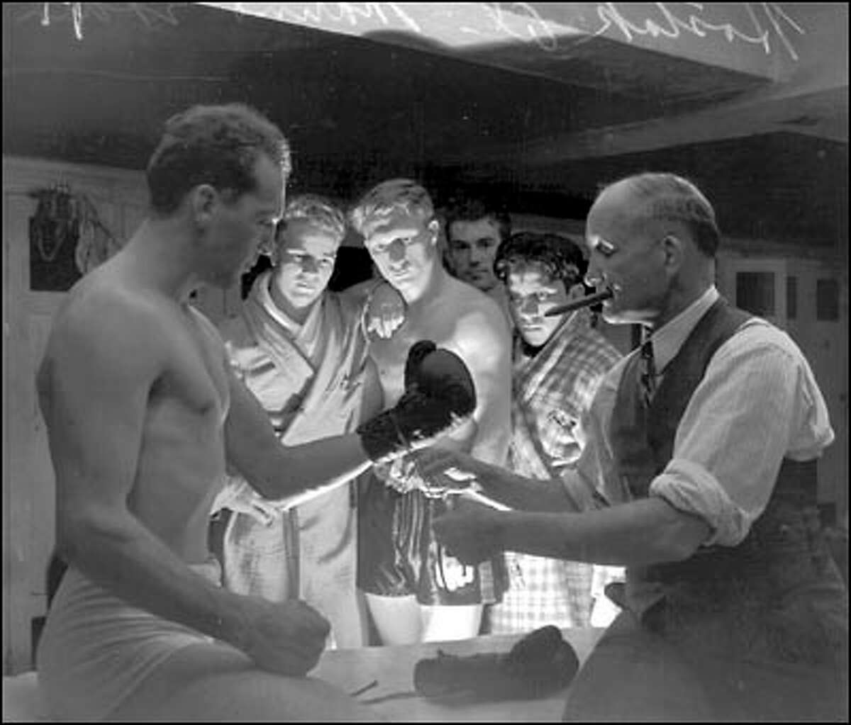 """Cigar-chomping trainer Eddie Marino laces up a glove on middleweight titleholder Al Hostak for his Sept. 18, 1938 bout with Young Stuhly at Seattle's Civic Auditorium. Frank """"Slim"""" Lynch lit the scene from below so that a ghostly light plays over the scene."""
