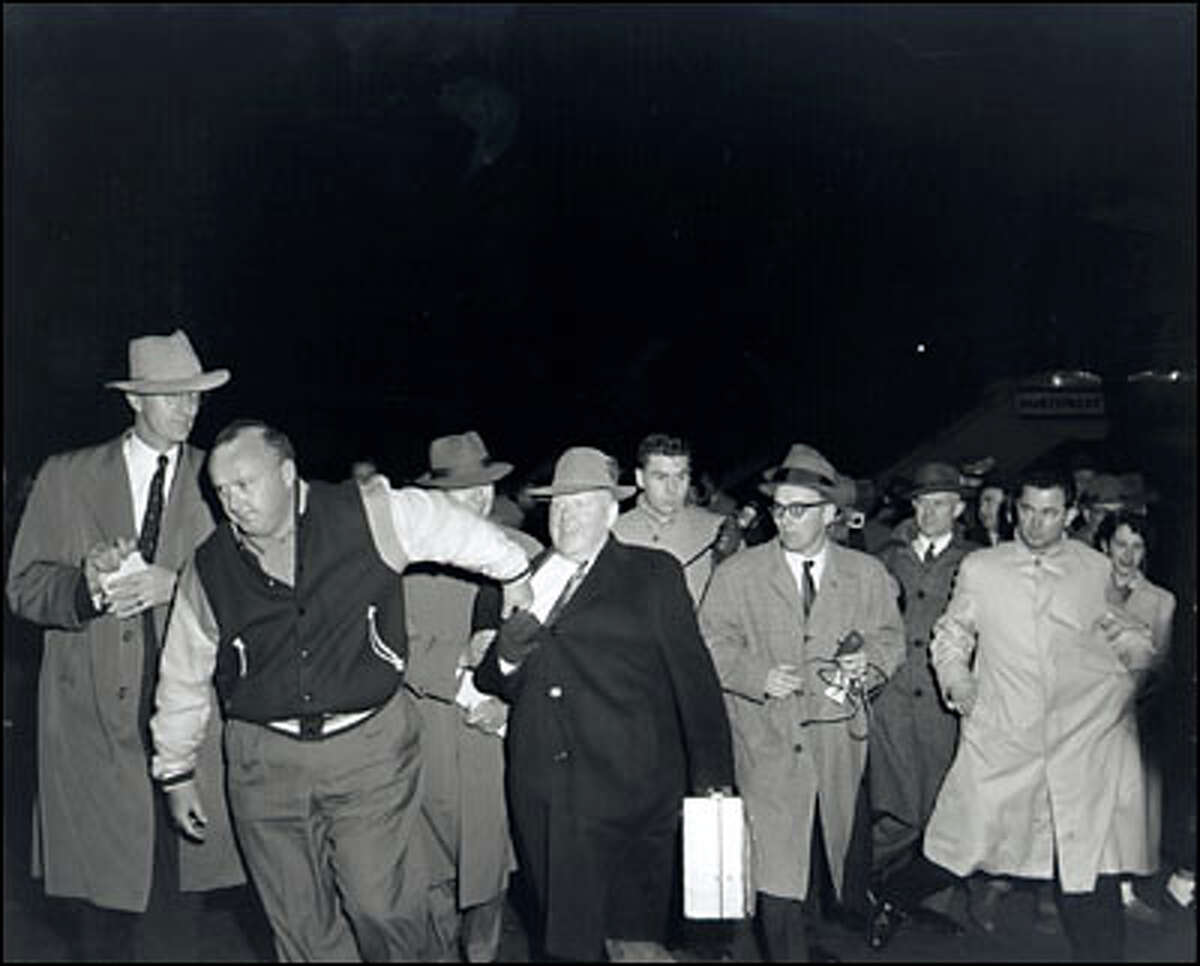 March 19, 1957, Dave Beck Jr., tries to pull his father away from reporters on arrival at Sea-Tac Airport. Beck Sr., president of the Teamster Union, was ordered to appear before the Senate Labor Rackets Committee and produce his personal financial records. The Committee was investigating the use of funds by prominent labor officials.