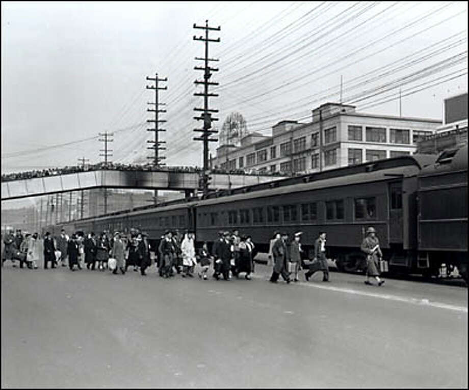 "March 30, 1942, the first group of Japanese Americans from Bainbridge Island board a waiting train at the Seattle waterfront as a crowd watches from an overpass.  The 225 men, women and children, described in the newspaper caption as ""bewildered but unprotesting...on their way to a strange land, "" were sent to Manzanar, an internment camp in the California desert. Photo: Seattle Post-Intelligencer"
