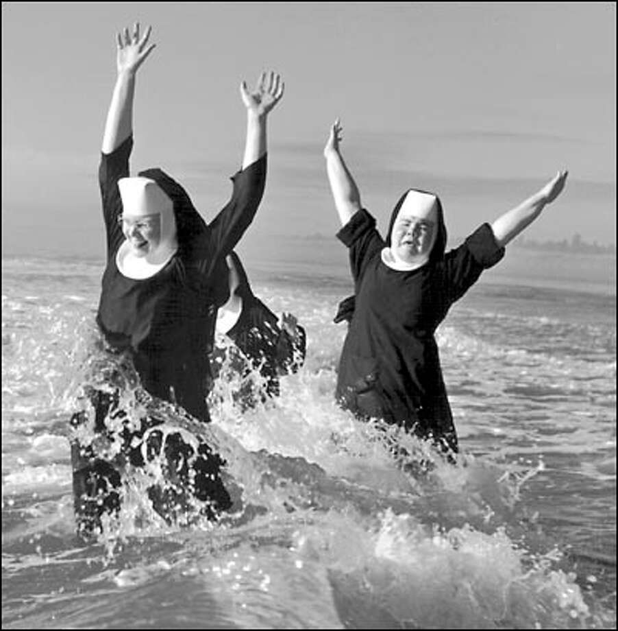 Childlike glee takes flight when a trio of nuns from the Order of St. Benedict make a splash in the Pacific Ocean while vacationing at Grayland in 1960. The photographer was Tom Brownell. Photo: Seattle Post-Intelligencer