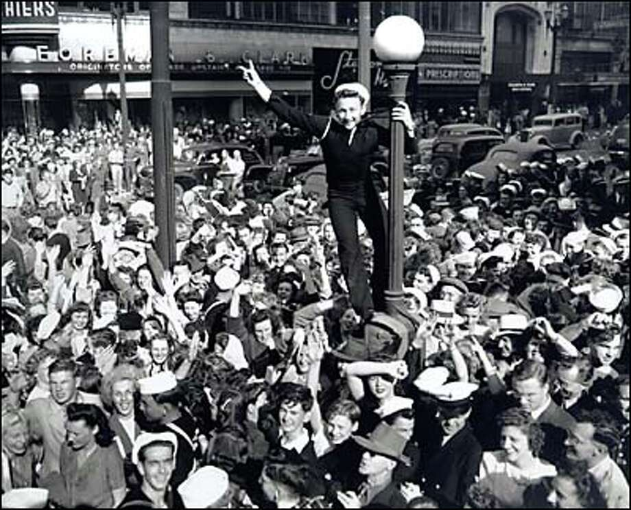 "Celebration of V-J Day, August 15, 1945. As sirens announced the end of World War II, merrymakers in a ""rooting, tooting, honking mass"" spilled onto the streets of downtown Seattle.  Civilians and servicemen, including several Navy men from Bremerton, came together in a joyous and uninhibited crowd. One sailor leaped onto a lamppost and waved as the photographer caught the moment. Many years later, O.F. ""Ole"" Scarpelli, Sergeant-at-Arms for the State Legislature, identified himself as that sailor, claiming he was ""just showing off"" on that remarkable day. Photo: Seattle Post-Intelligencer"