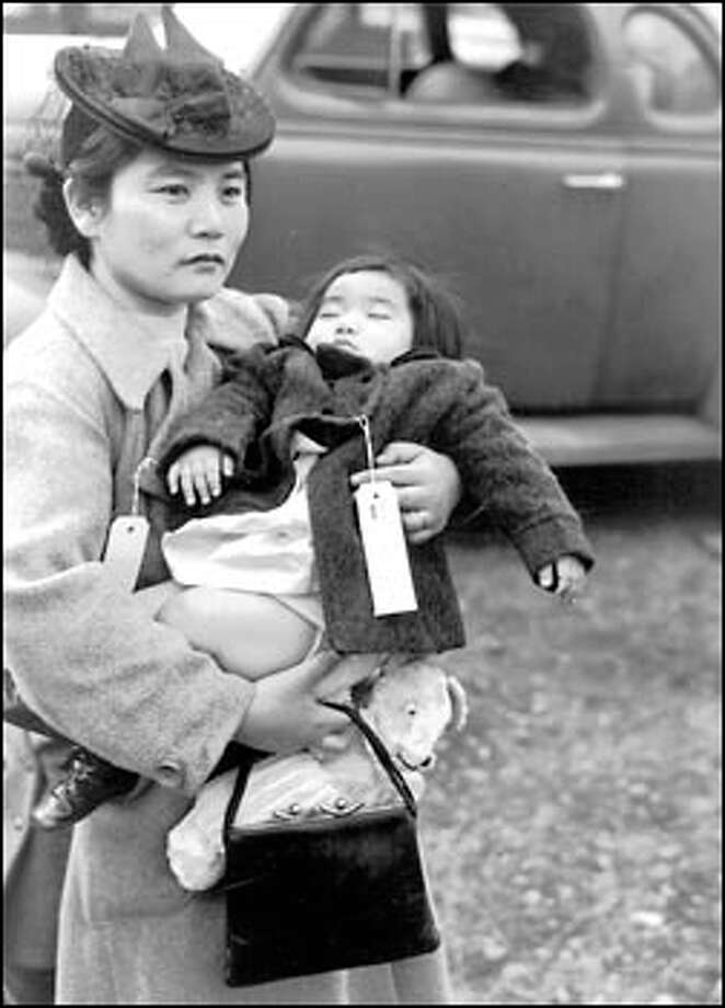Her 11-month-old daughter asleep in her arms, Fumiko Hayashida waits to board a ferry from Bainbridge Island on March 30, 1942. But it's no pleasure trip: The pair are being shipped to an internment camp for Japanese Americans in Manzanar, Calif. Photo: Seattle Post-Intelligencer