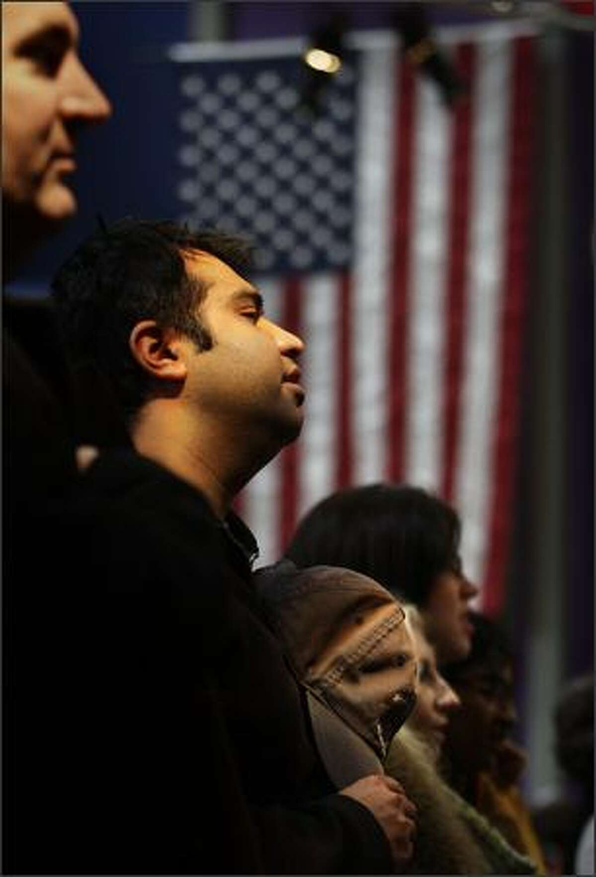 Rashi Batra and others gather at Center House at the Seattle Center listen to the national anthem during a live telecast of Barack Obama's inauguration ceremony.