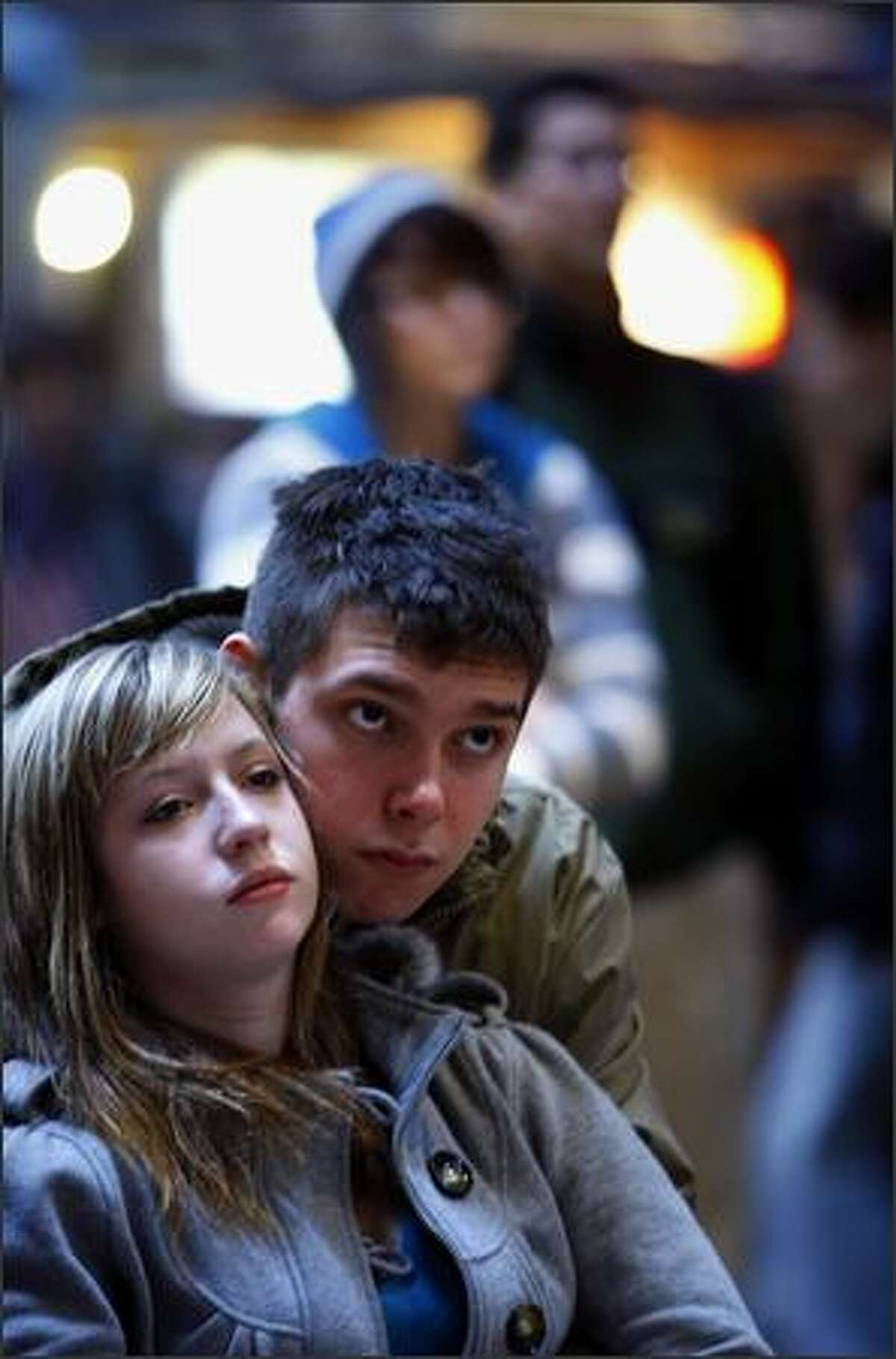 Rose Parsons and Josh Carvajal, both 17 of Seattle, watch a live telecast of Barack Obama's inauguration ceremony with a crowd at Center House in Seattle Center on Tuesday.