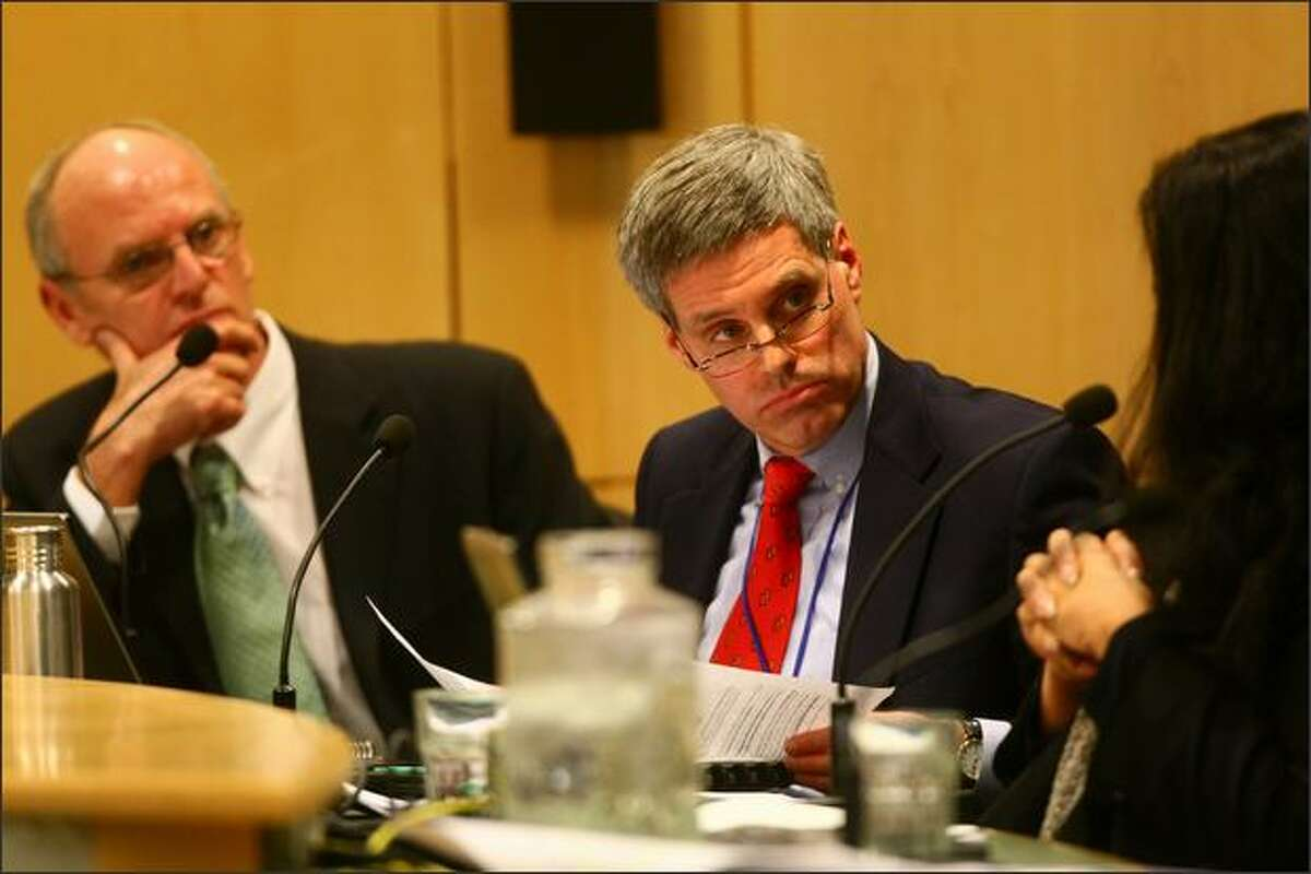 Board members Michael DeBell, left, and Steve Sundquist listen to director Mary Bass.