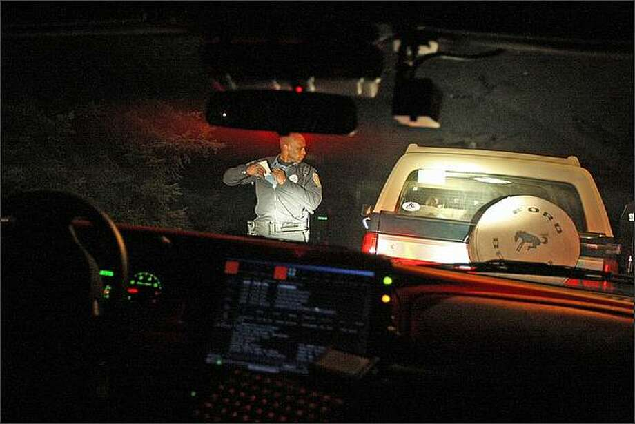 Seattle Police Officer Adley Shepherd was the subject of a 2009 photo essay published by Seattle P-I. Those file photos follow. He is pictured above walking back to his patrol car after making a traffic stop while on patrol in the south end of Seattle Photo: Mike Kane, Seattle Post-Intelligencer