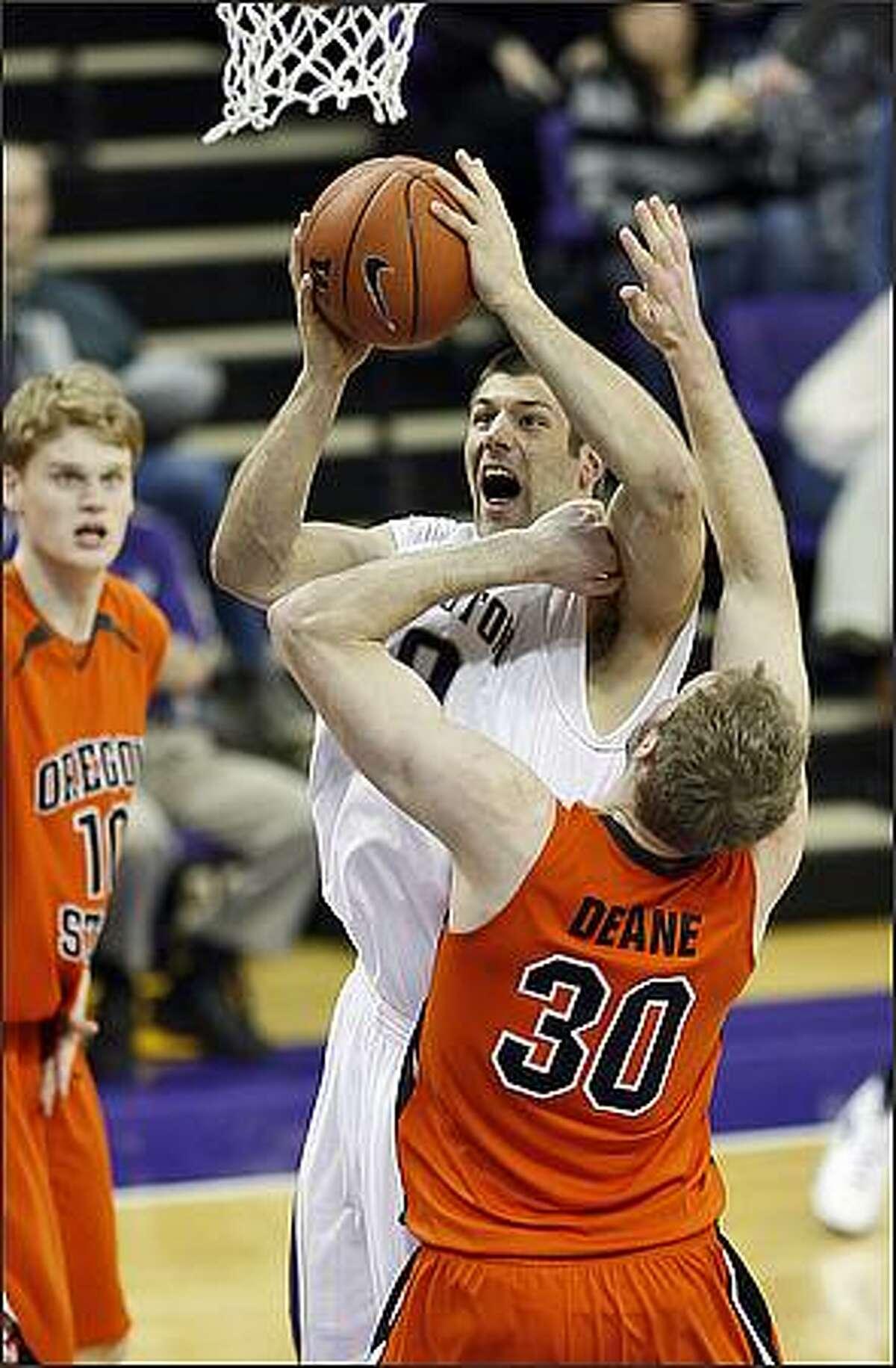 Washington Huskies Jon Brockman shoots over Oregon State Beavers Daniel Deane during first half action at the University of Washington.