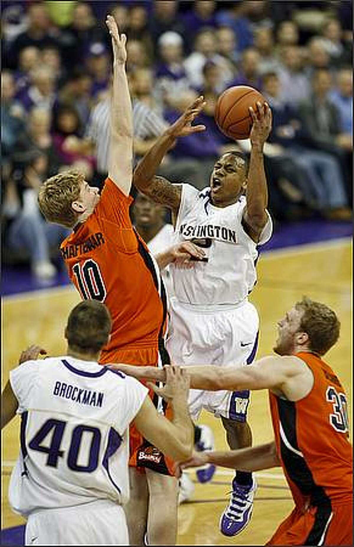 Washington Huskies Isaiah Thomas' run at the hoop is thwarted by Oregon State Beavers Roeland Schaftenaar (10) during first half action at the University of Washington.