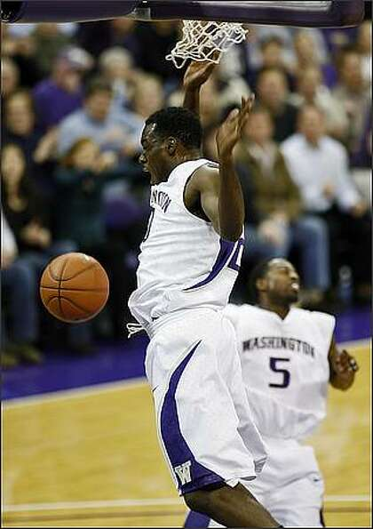 Washington Huskies Quincy Pondexter fires up the Husky crowd and team with a slam near the end of fi