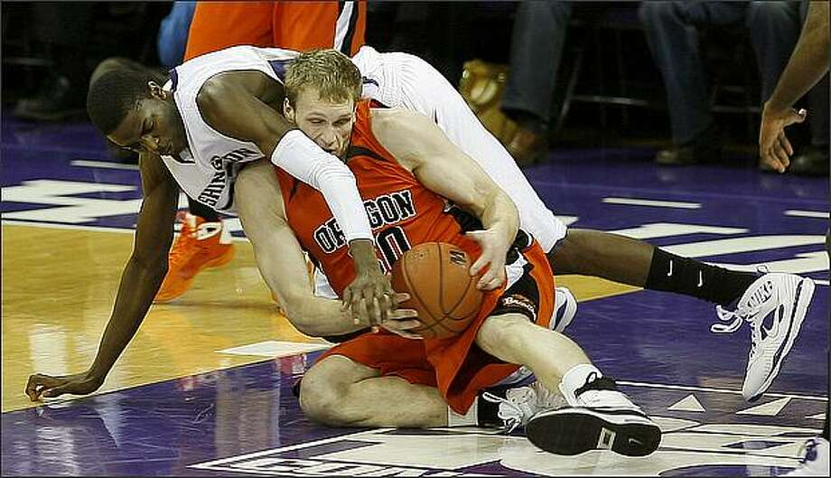 Washington Huskies Justin Holiday reaches for the ball over Oregon State's Daniel Deane during first half action at the University of Washington. Photo: Mike Urban, Seattle Post-Intelligencer