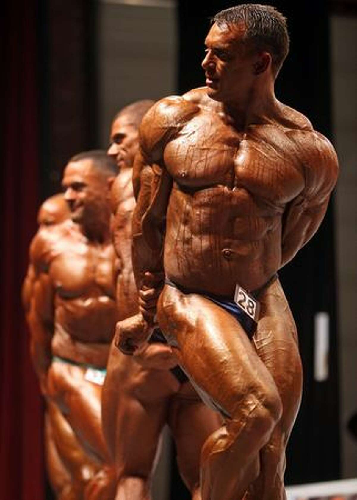 Bodybuilders pose for judges in the preliminary rounds of The Mister Universe competition at The Southport Theatre Saturday in Southport, England. Bodybuilders from all over the world are competiting for the National Amateur Body Building Association titles with their sculptured and honed bodies.