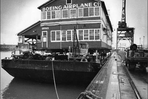 "Boeing's ""Red Barn,"" vintage 1910, was loaded aboard a Foss barge on Dec. 16, 1975 for a trip down the Duwamish from Terminal 115 to a new museum-site home on the southwest corner of Boeing Field. The original Boeing Plant was designated a National Historical Place. (P-I photo by Cary Tolman)"