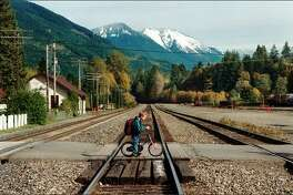 Nicholas Robinson,10, crosses the tracks that divide the town of Skykomish, on his way home from school. The trains, which no longer stop there, thunder through town 29 times-a-day.(P-I photo by Meryl Schenker)