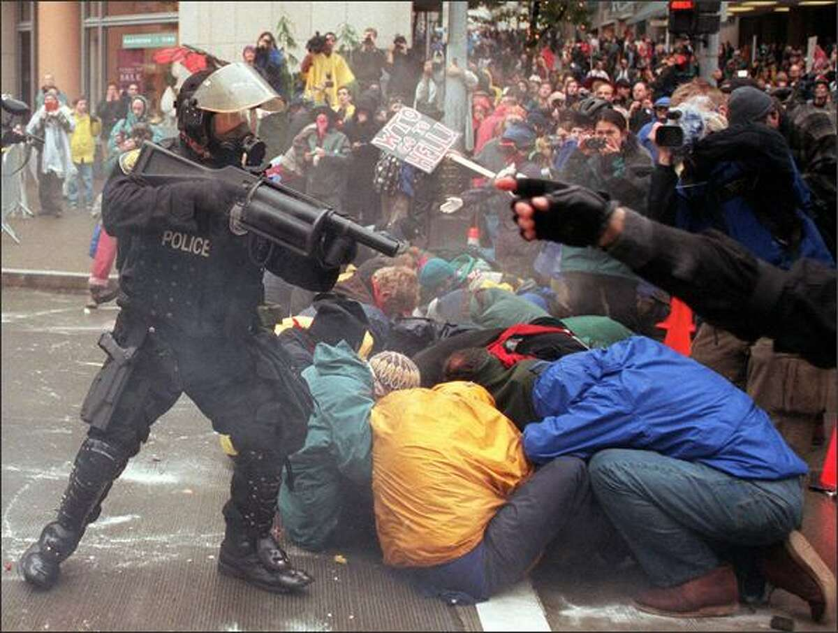 A Seattle police officer shoots rubber pellets at a group of anti-WTO demonstrators at Sixth and Pine who were attempting to block public access to the Washington State Convention and Trade Center on Nov. 30,1999. Protestors forced cancellation of of the World Trade Organization's opening ceremonies at the Paramount Theater. (P-I photo by Paul Joseph Brown)