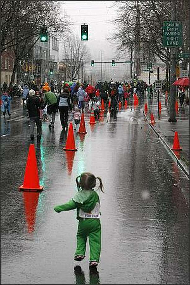 Odeit Fanning of Bothell, 2, runs down Mercer Street during the kids portion of the St. Patrick's Day Dash. Photo: Meryl Schenker, Seattle Post-Intelligencer