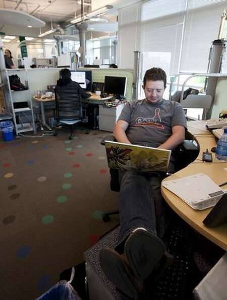 Google software engineer Greg Millam works at his desk at Google Kirkland on Wednesday.