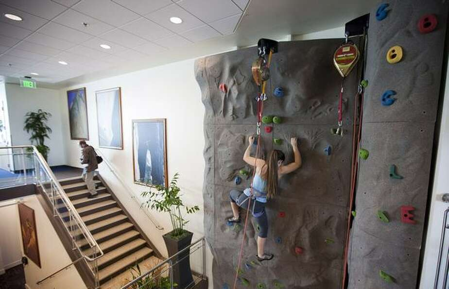 Google software engineer Amanda Camp demonstrates the climbing wall during the grand opening of Goog