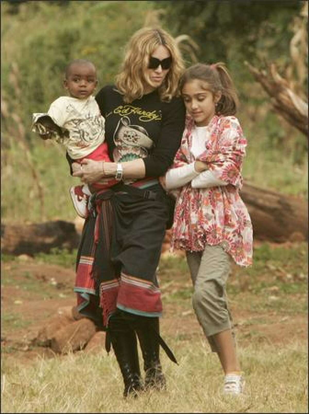 Madonna carries her adopted son David at the Home of Hope orphanage in Mchinji village, Malawi, April 17, 2007. Malawi police and stone-throwing school students blocked journalists from covering the pop star's visit to the orphanage, where the boy was due to meet his biological father. At right is Madonna's daughter Lourdes.