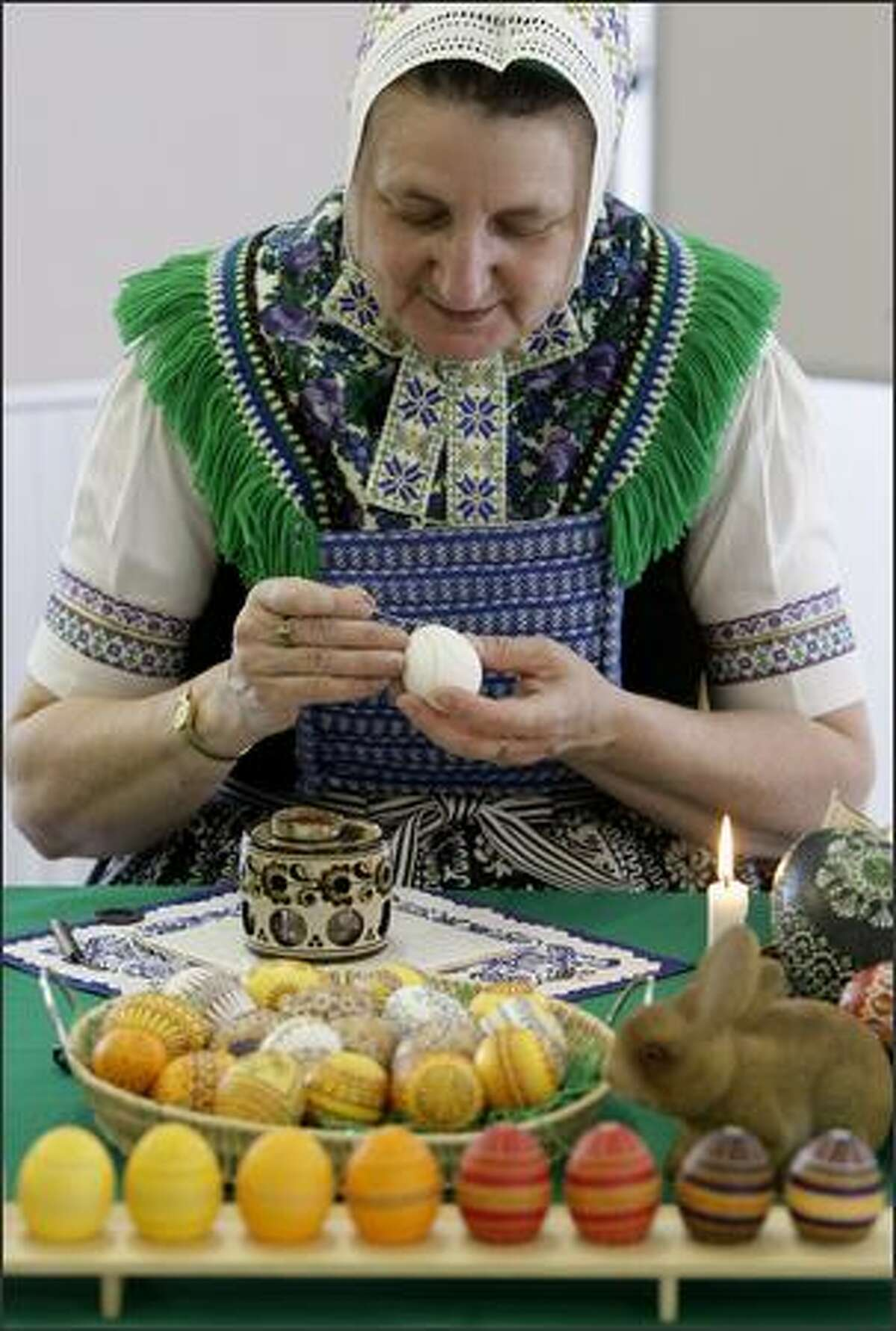 Petra Nakoinz, dressed in a regional Sorbic dress, works on a traditional Easter egg in the eastern German village of Schleife.