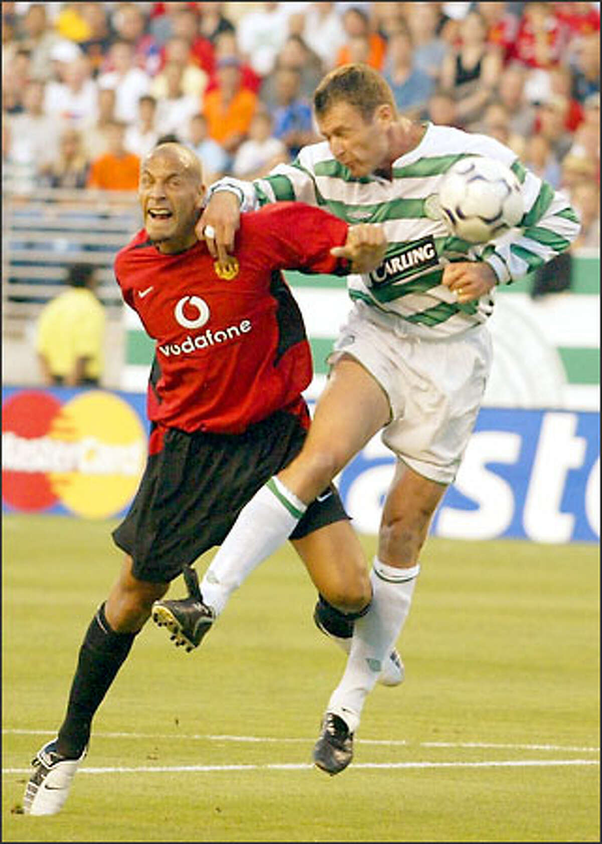 Manchester United's Rio Ferdinand, left, and Celtic's Chris Sutton battle for the ball during the first half.