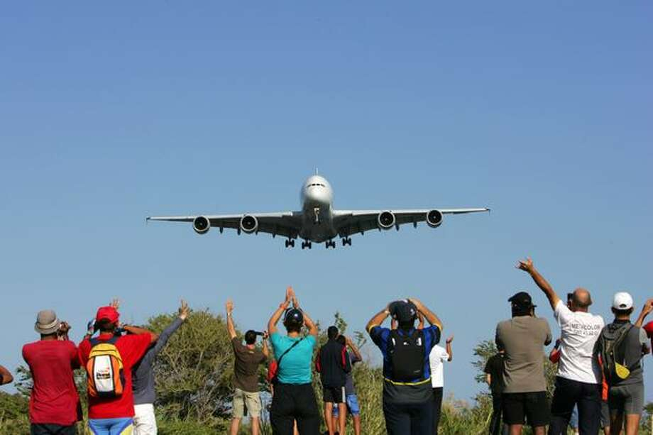 People watch as an Airbus A380 flies over the Indian ocean island of La Réunion during an exhibition flight before landing at the Roland-Garros airport on November 11, 2009 near the city of Saint-Denis-de-la-Réunion. The local airline company Air Austral has ordered two of the aircraft. Photo: Getty Images