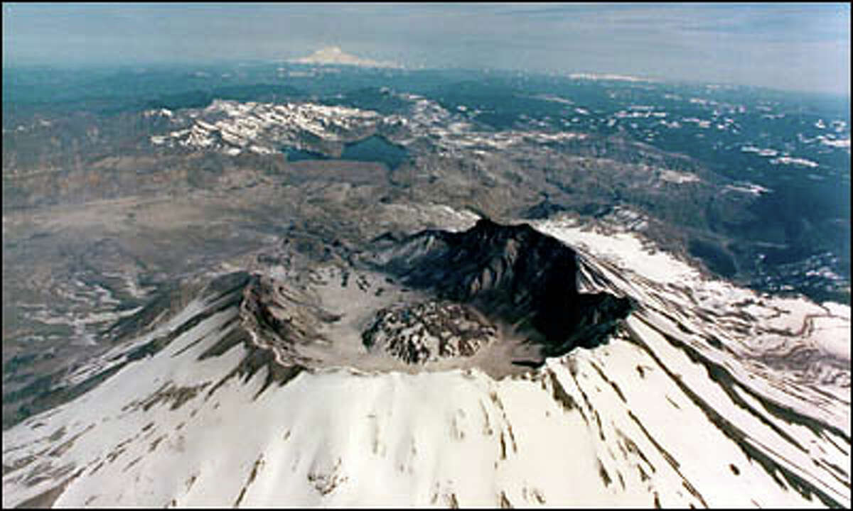 Mount St. Helens sports a snowy cover in this 1990 photo, taken after heavy rains touched off a huge landlside in the crater and pushed sediment all the way to Spirit Lake. Mount Rainier is in the distance.