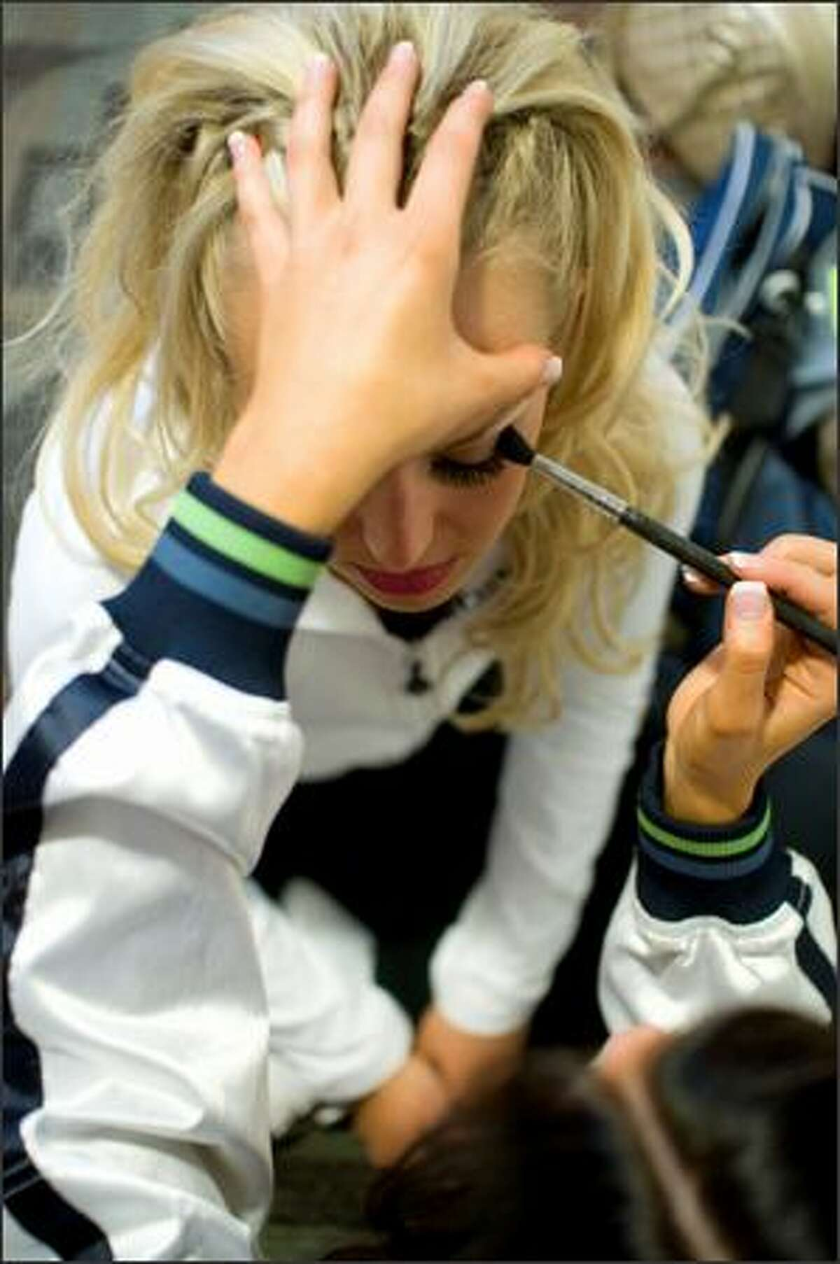 Brittany Wood gets her makeup done with a little help from friend Nicole Perry during final tryouts for the Sea Gals at Qwest Field. (Daniel Berman / Special to SeattlePI.com)