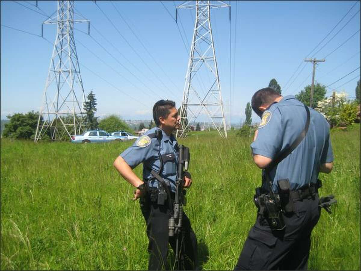 South Precinct officers talk during a police search for a bear reported Thursday morning on Beacon Hill. Capt. Les Liggins said the officers were armed with rifles as a safety precaution.