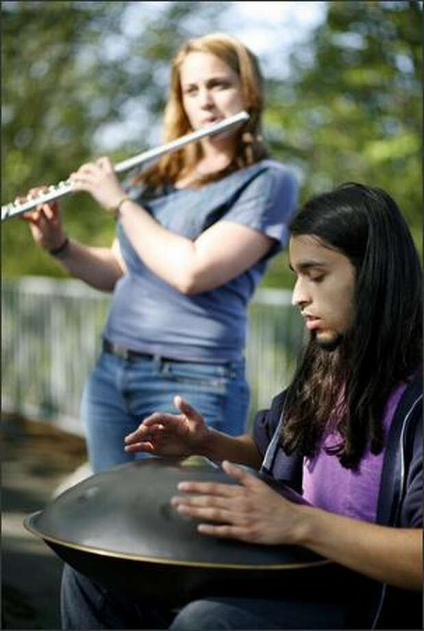 Ehssan Karimi plays a hang drum while Jess Wilkes accompanies him on flute. Photo: Joshua Trujillo, Seattlepi.com