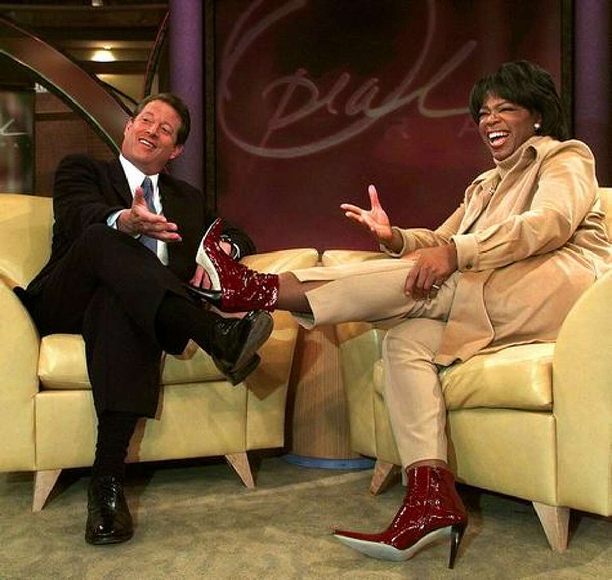 Former U.S. Vice President and (at the time) Democratic presidential candidate Al Gore (L) compares shoes as he talks with US talk show host Oprah Winfrey just after he appeared on her show in Chicago, Illinois, September 11, 2000.