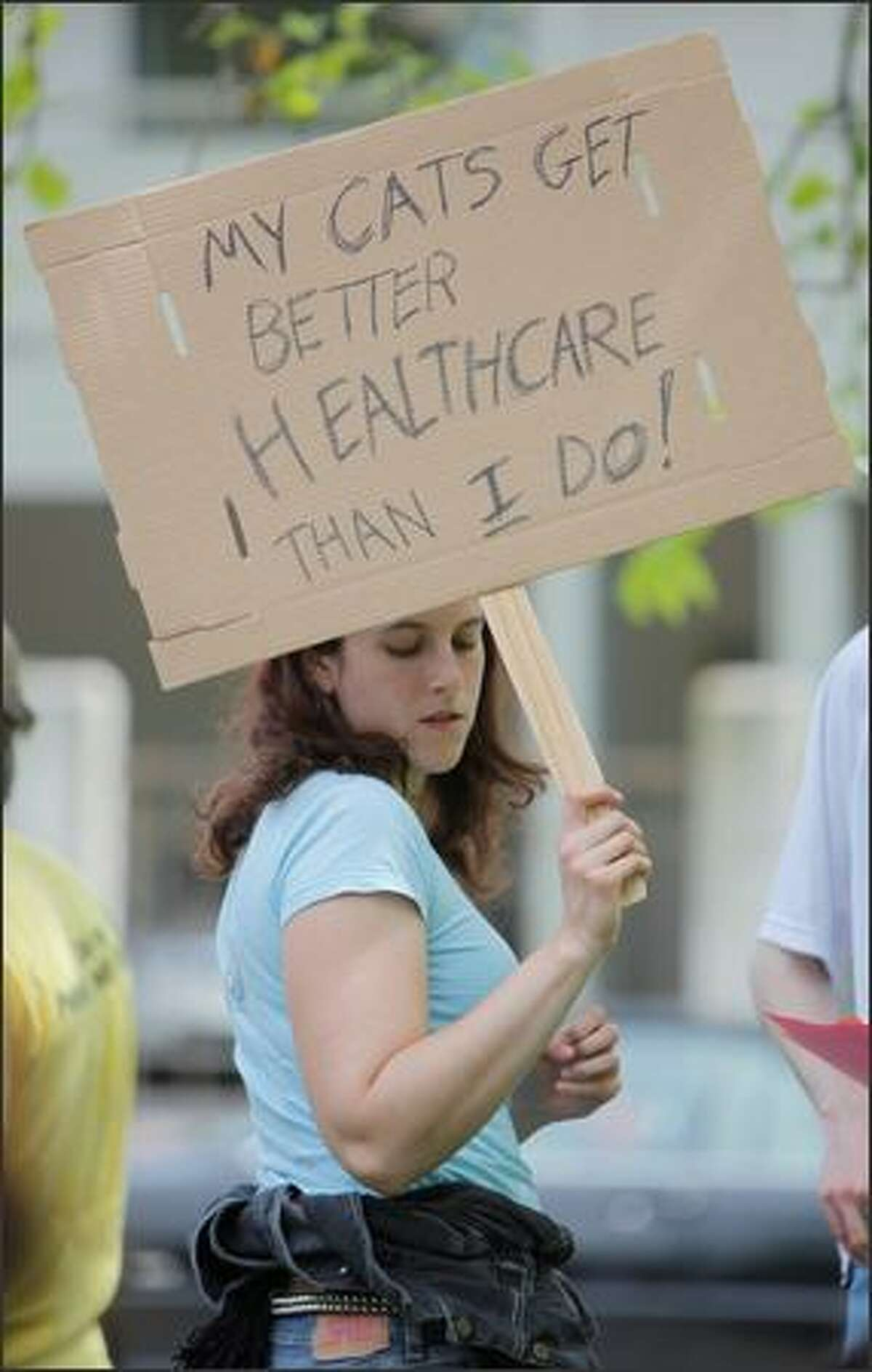 Sarah Silverman of Seattle holds a sign stating that her cats get better health care than she does.