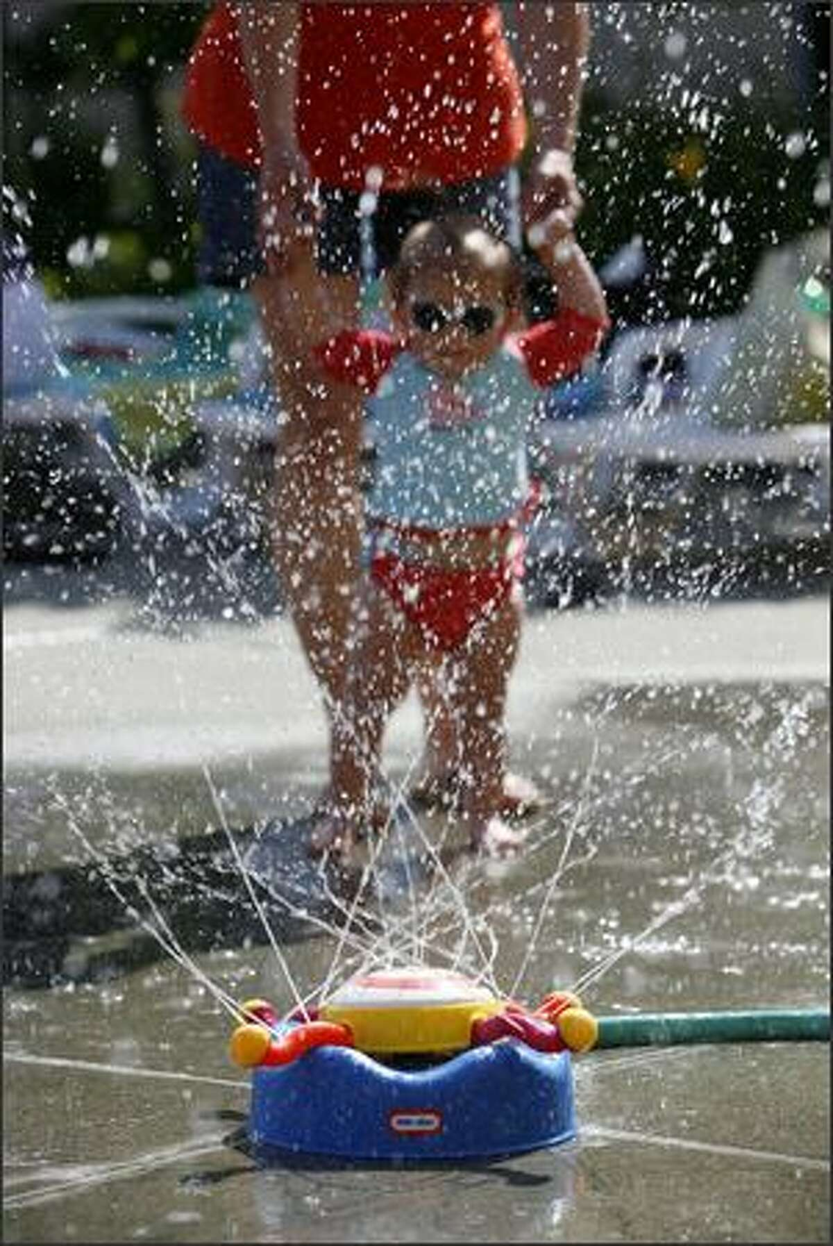 Raven Willis, 1, watches a sprinkler cool children playing at the Mounger Pool in Magnolia on Wednesday.