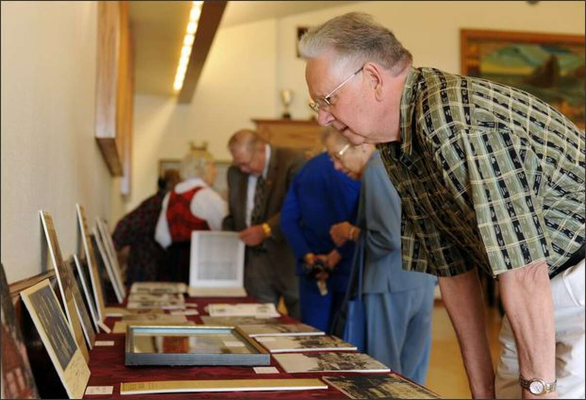 Bill Alsvik, a member of the Leif Erikson Lodge for 58 years, looks at old pictures and artifacts of the lodge shown at the opening of the time capsule.